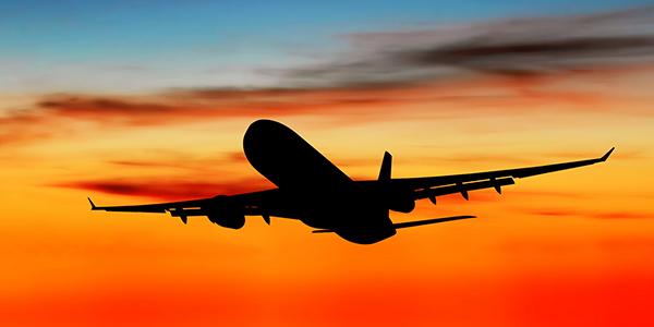 avião voando perto do por do sol