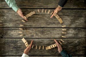 mãos que param peças de dominó caindo em cadeia